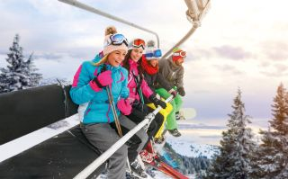 cheerful friends are lifting on ski-lift for skiing in the mount
